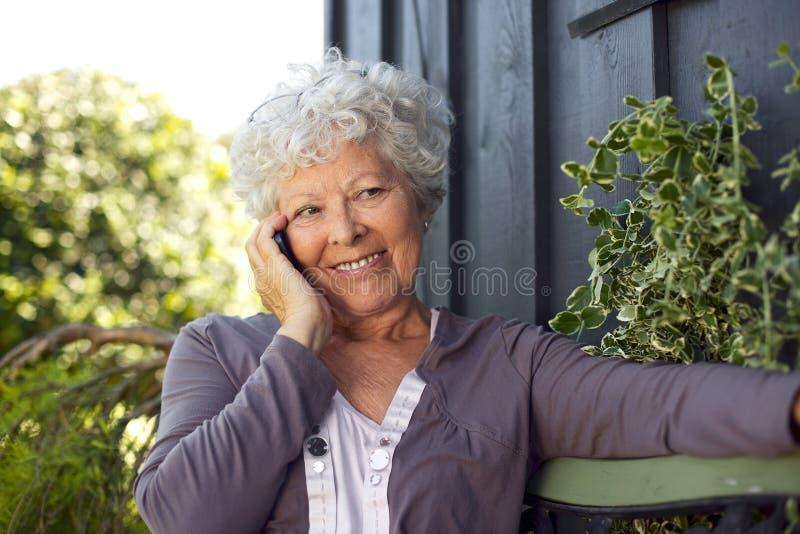 Счастливая пожилая женщина звоня телефонный звонок стоковые фото
