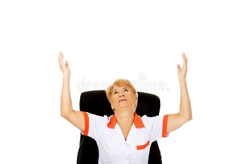 Счастливая пожилая женщина сидя за столом с руками вверх стоковая фотография