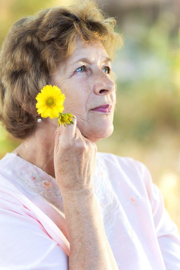 Счастливая пожилая женщина с цветками стоковые изображения