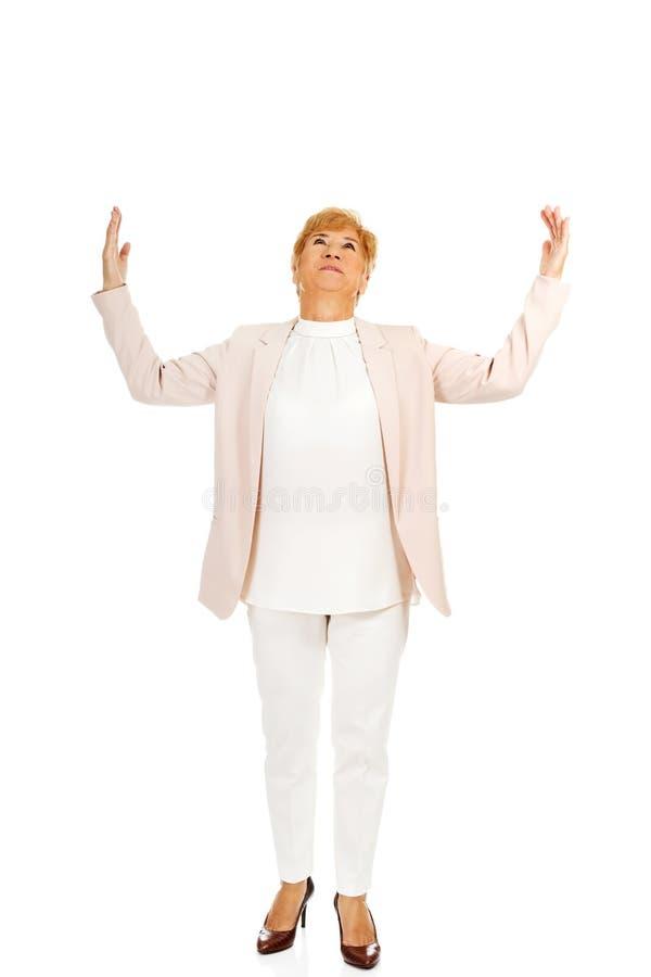 Счастливая пожилая попытка бизнес-леди для того чтобы уловить что-то стоковая фотография rf