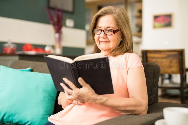 Счастливая постаретая женщина читая ее любимую книгу стоковое фото rf