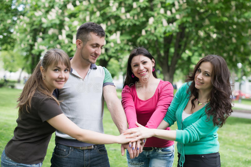 Счастливая подростковая группа с руками на стоге стоковое фото