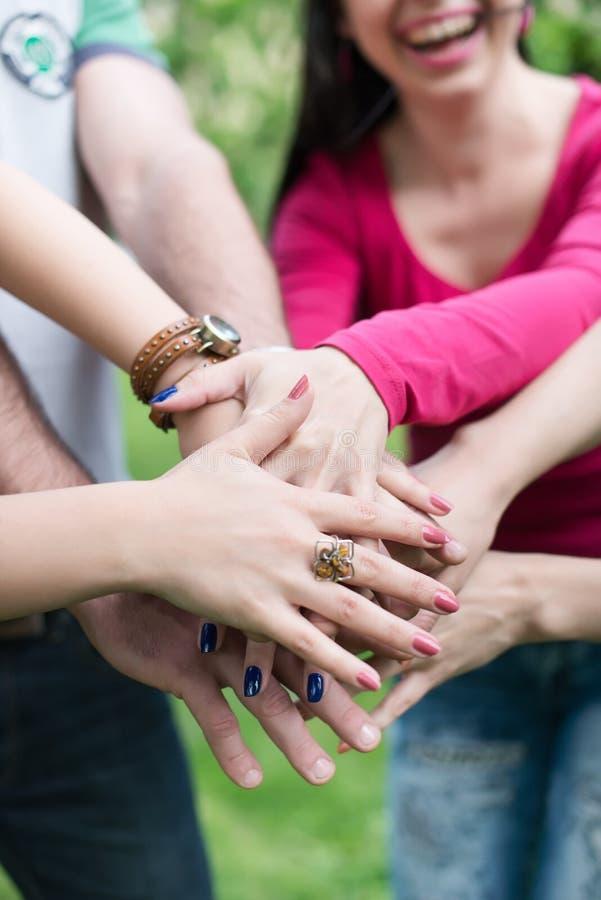 Счастливая подростковая группа с руками на стоге стоковая фотография rf