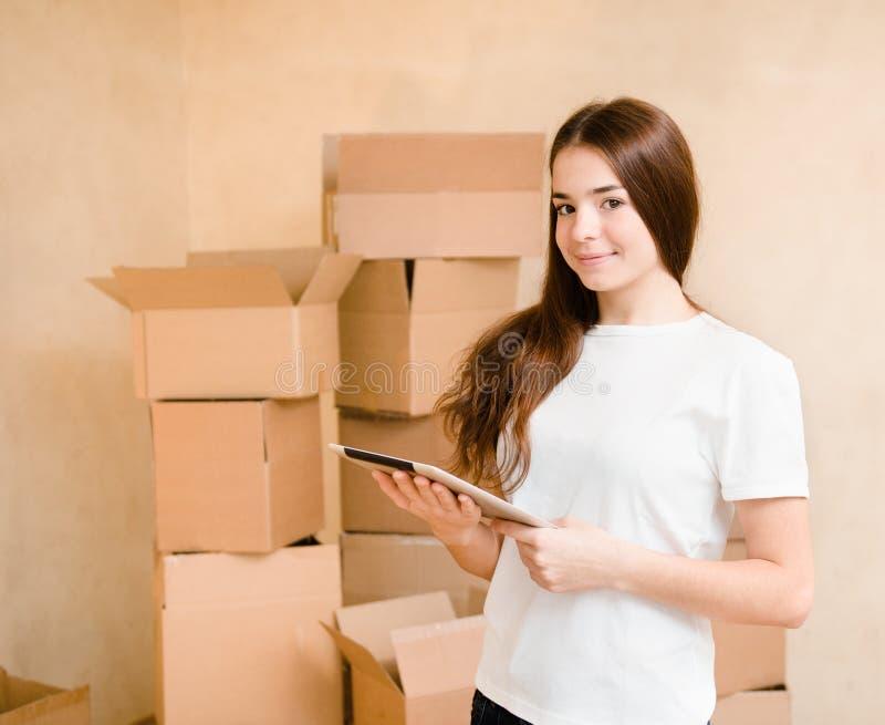 Счастливая предназначенная для подростков девушка при планшет стоя на предпосылке картона стоковое фото rf