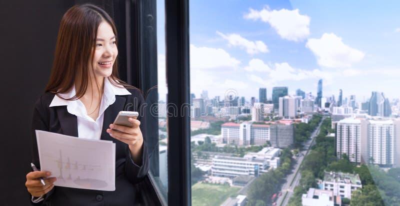 Счастливая привлекательная азиатская коммерсантка в костюме стоя в ей  стоковые фотографии rf