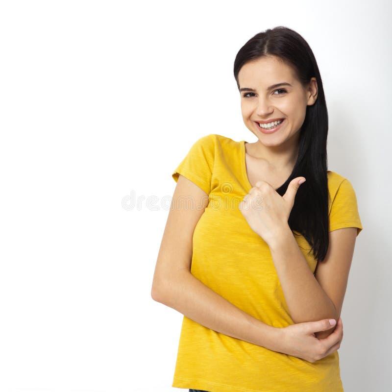 Счастливая привлекательная молодая женщина показывая большие пальцы руки вверх, о'кей изолировано стоковое фото rf