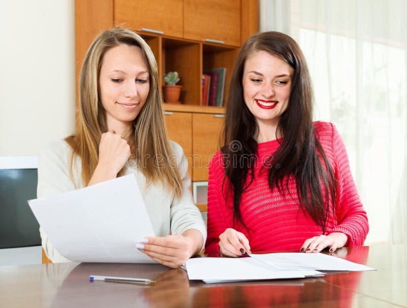 Счастливая работа девушек с документами стоковое фото