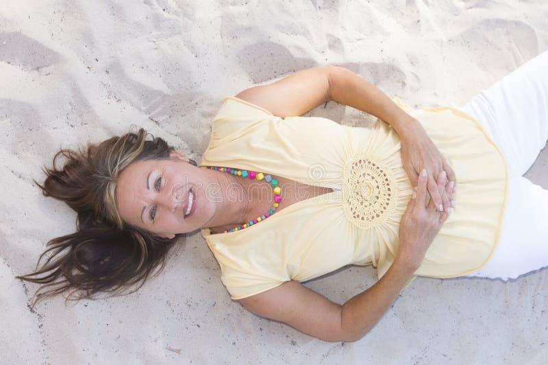 Счастливая расслабленная старшая женщина лежа в песке стоковая фотография rf