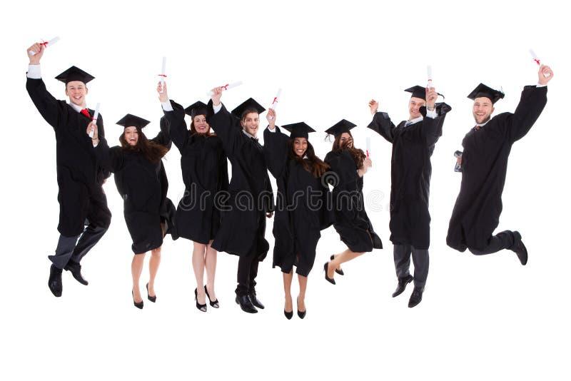 Счастливая радуясь группа в составе многонациональные студент-выпускники стоковая фотография rf