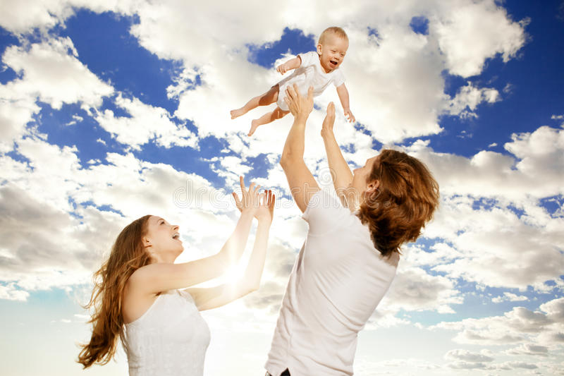 Счастливая семья бросает вверх ребёнок против голубого неба стоковое изображение