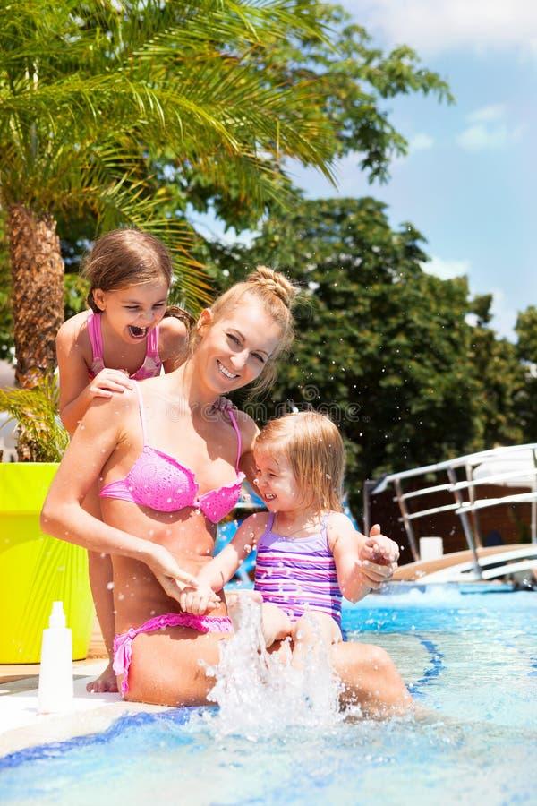 Счастливая семья в бассейне, имеющ потеху, концепцию каникул стоковое фото rf