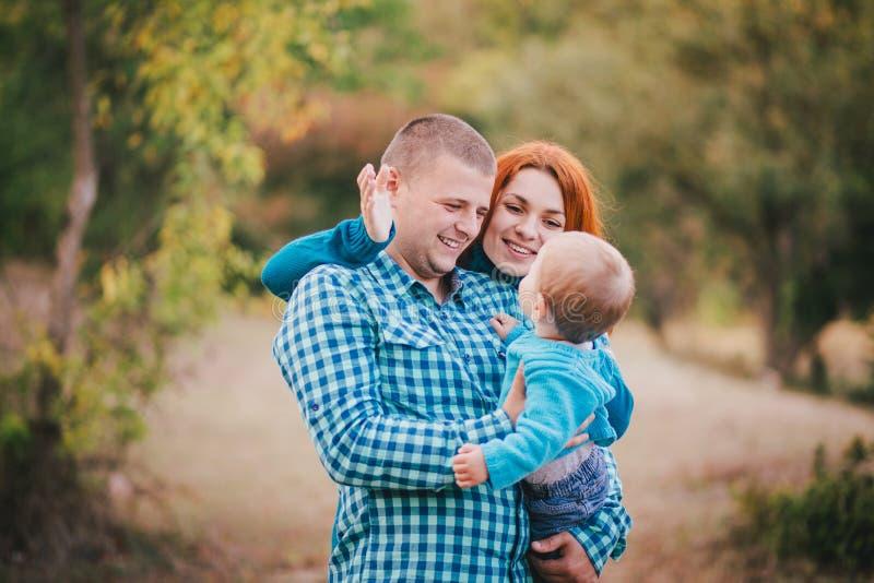 Счастливая семья в голубых стильных одеждах идя в лес осени стоковая фотография