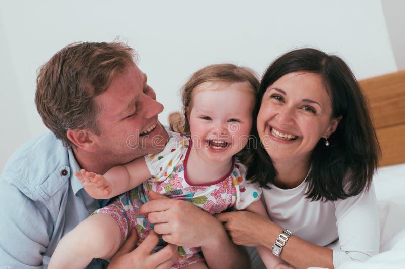Счастливая семья в кровати стоковое фото