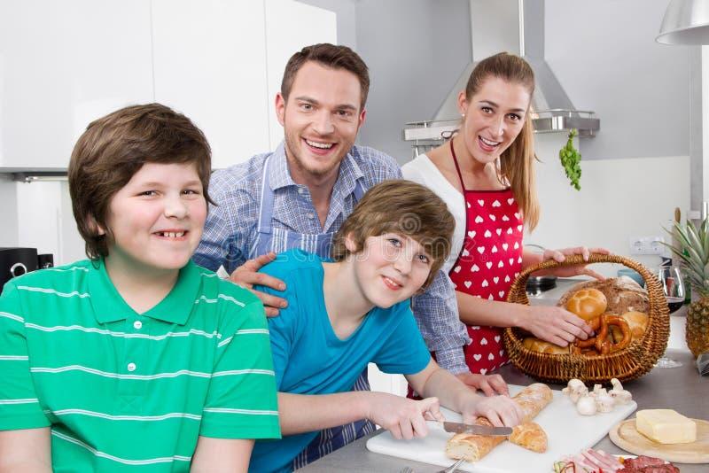 Счастливая семья в кухне подготавливая завтрак в воскресенье стоковые изображения
