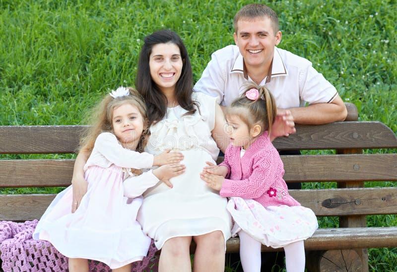 Счастливая семья в парке города лета внешнем, беременная женщина, родитель и дети, яркий солнечный день и зеленая трава, красивые стоковые изображения