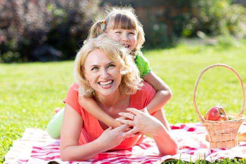 Счастливая семья лежа в траве в лете или стоковая фотография rf