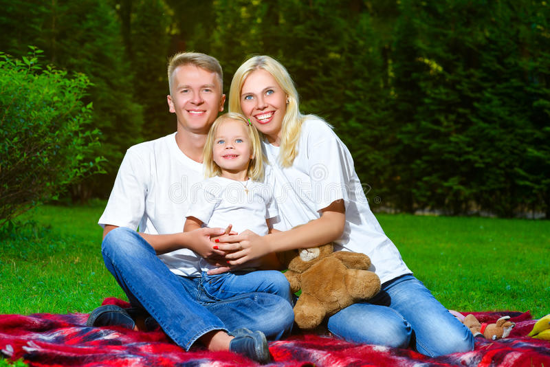 Счастливая семья лежа на траве в лете Пикник стоковая фотография rf