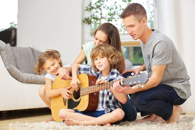 Счастливая семья делая музыку с гитарой стоковое фото