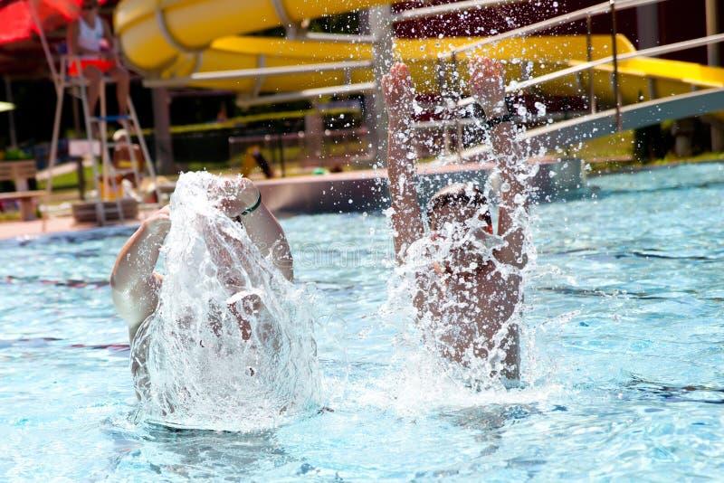 Счастливая семья играя в плавательном бассеине стоковое фото rf