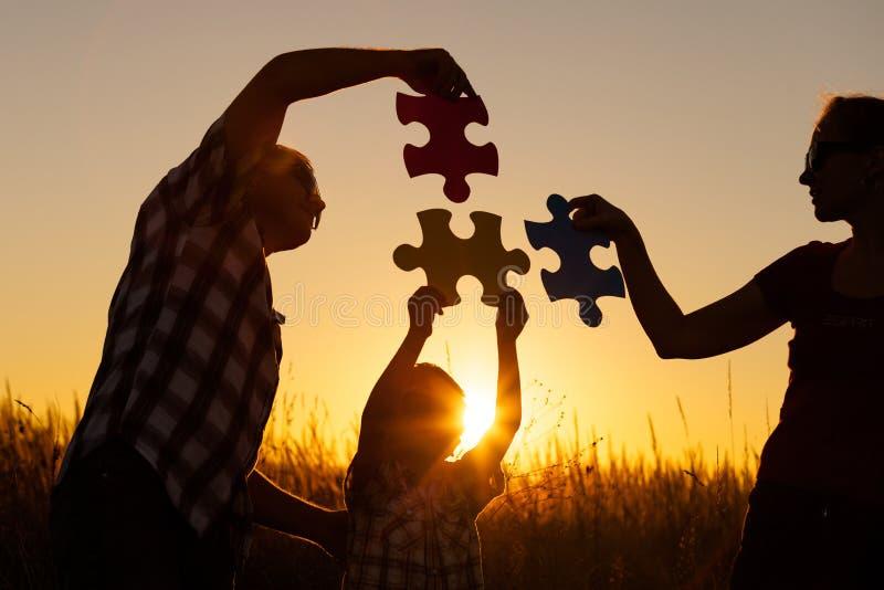 Счастливая семья играя на парке на времени захода солнца стоковые фотографии rf