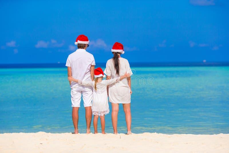 Счастливая семья из трех человек в шляпах Санты во время стоковые изображения rf