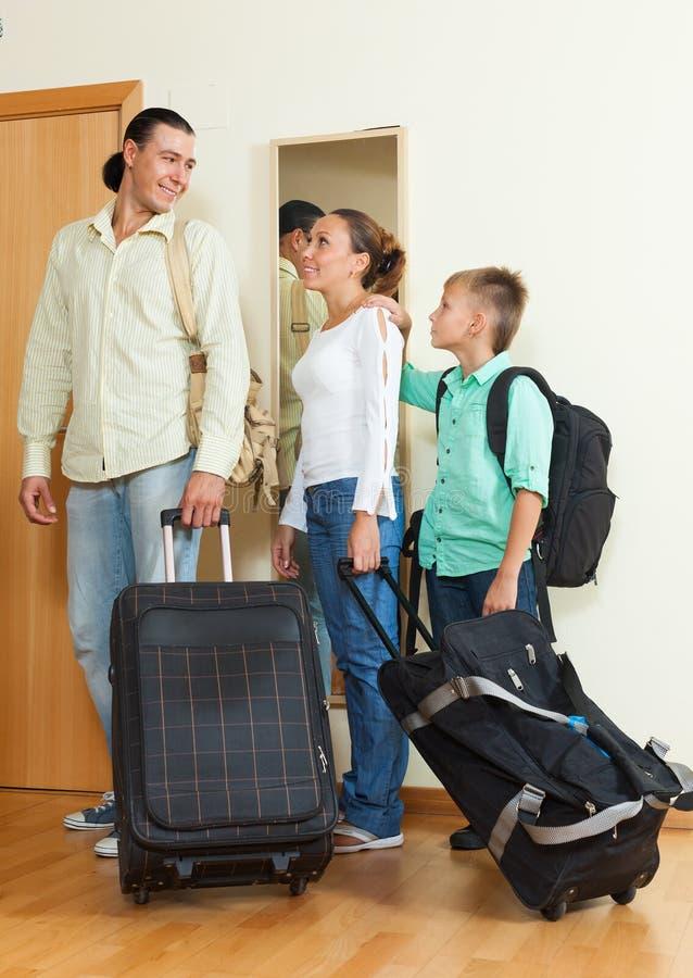 Счастливая семья из трех человек покидая дом стоковые изображения rf