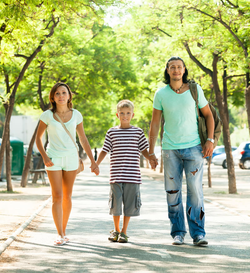 Счастливая семья из трех человек при подросток идя в парк стоковое изображение rf