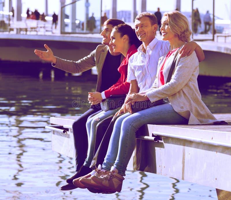 Счастливая семья из четырех человек наслаждаясь совместно около моря стоковая фотография