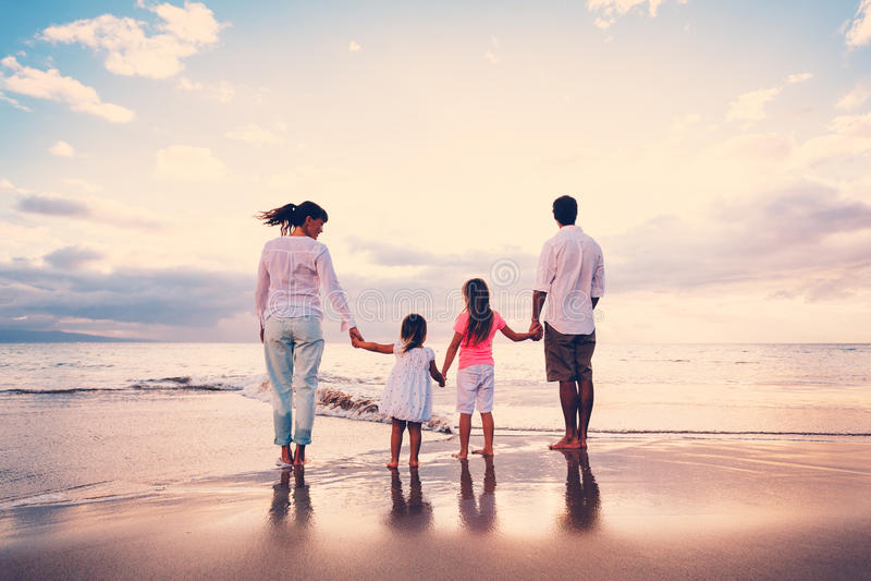 Счастливая семья имеет потеху идя на пляж на заходе солнца