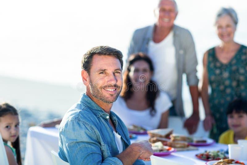Счастливая семья имея пикник на пляже стоковое фото rf