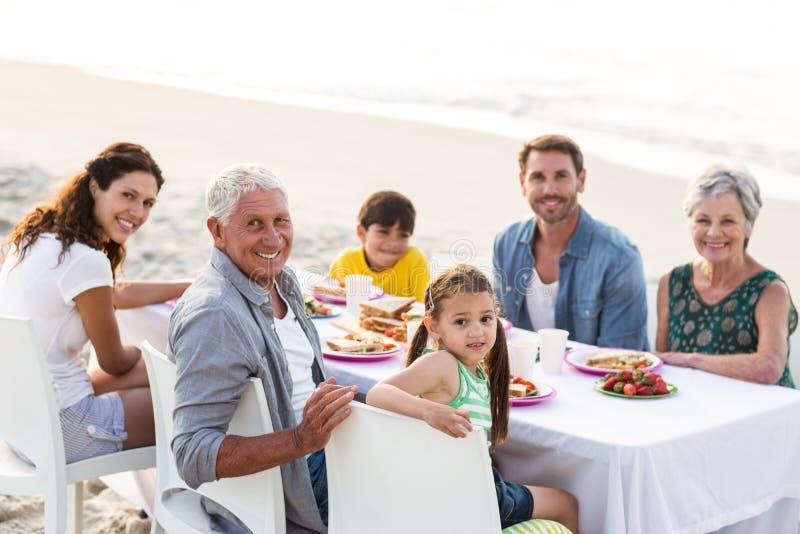 Счастливая семья имея пикник на пляже стоковое изображение rf