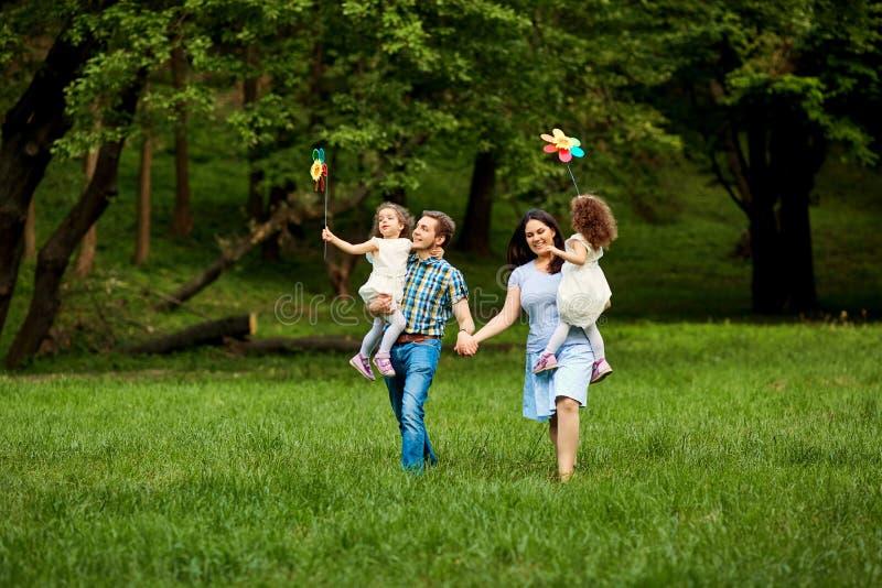 Счастливая семья идя в парк лета стоковое изображение rf