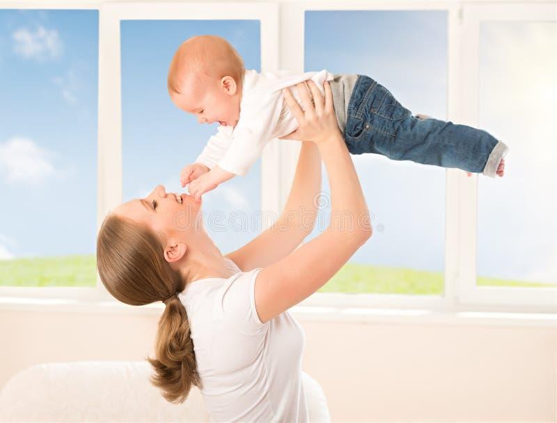 Счастливая семья. Мать бросает вверх младенца, играя стоковые изображения rf