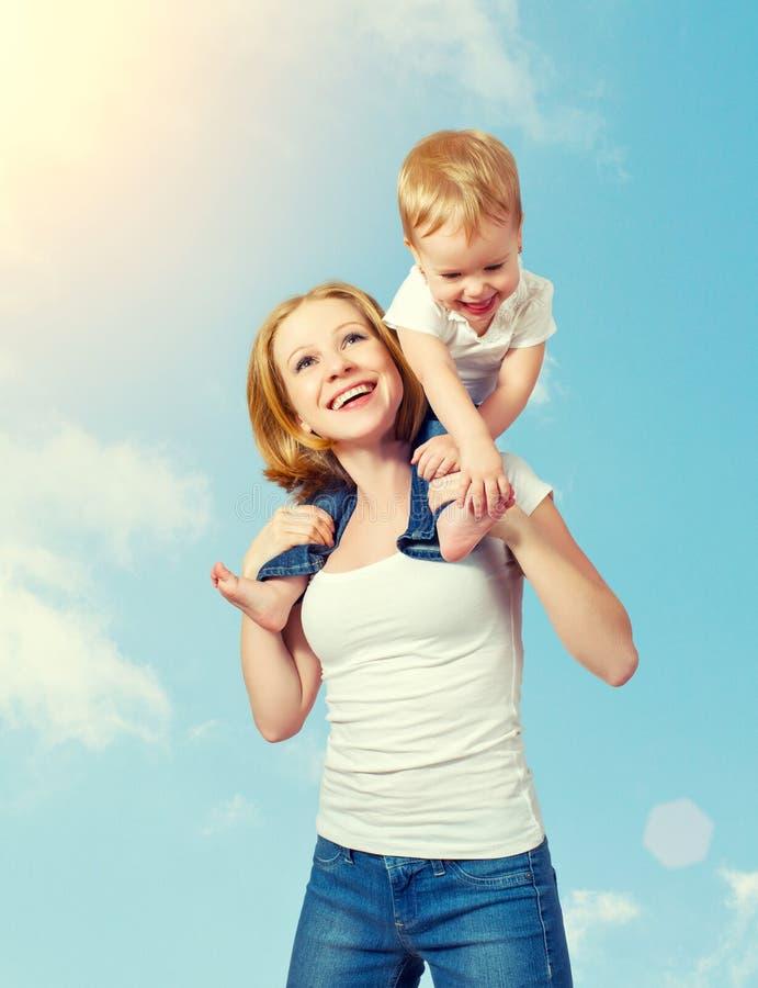 Счастливая семья. младенец сидит верхом на плечах матери и стоковая фотография