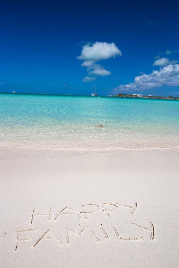 Счастливая семья написанная на тропическом песке белизны пляжа стоковое изображение rf