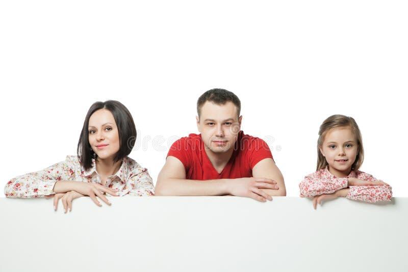 Счастливая семья над афишей стоковое фото