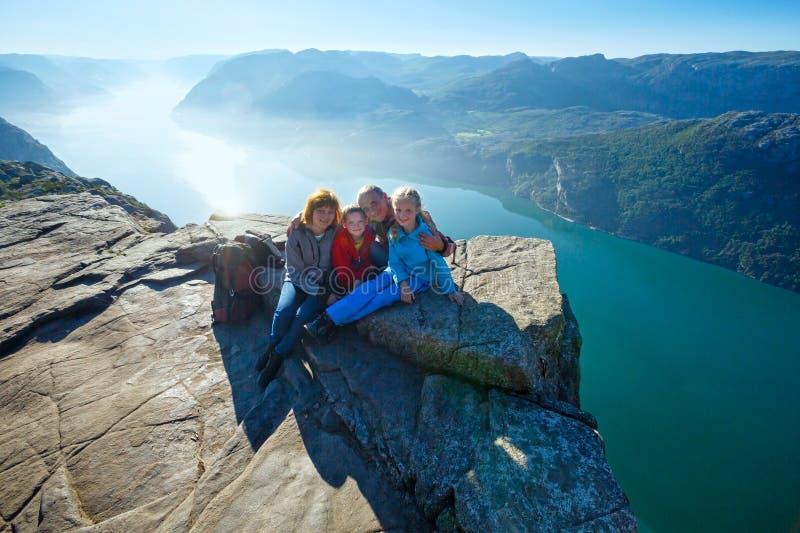 Счастливая семья на верхней части скалы Preikestolen массивнейшей (Норвегия) стоковые фотографии rf