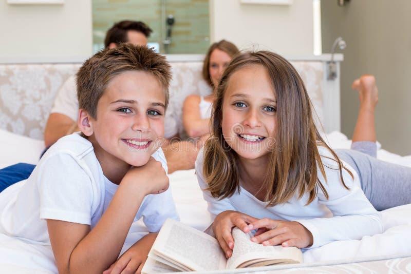 Счастливая семья на книге чтения кровати стоковая фотография