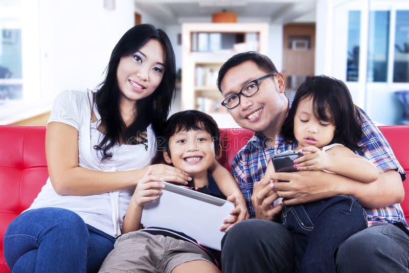 Счастливая семья на красной софе дома стоковые фото
