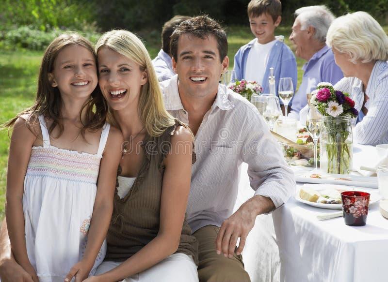Счастливая семья обедая на таблице в саде стоковые фото