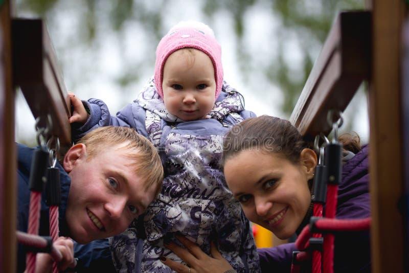 Счастливая семья: Отец, мать и дето- маленькая девочка идя в осень паркуют: mamy, младенец папы играя на спортивной площадке стоковая фотография rf