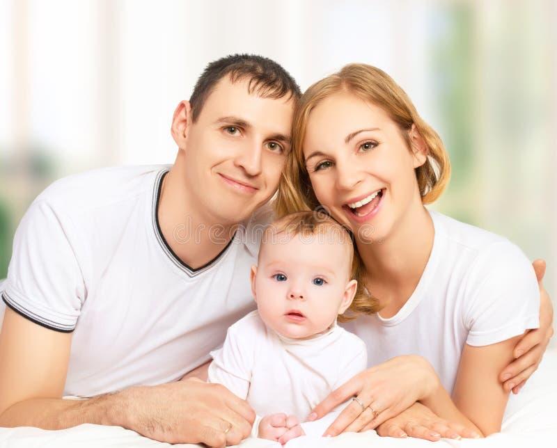 Счастливая семья отца, матери и малой дочери ребёнка внутри стоковое изображение