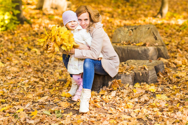 Счастливая семья: дочь матери и ребенка маленькая играет, смеющся над прижиматься на прогулке осени в природе outdoors стоковые фото