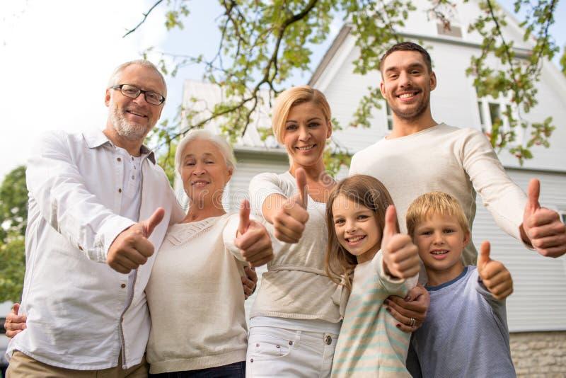 Счастливая семья перед домом outdoors стоковые изображения rf