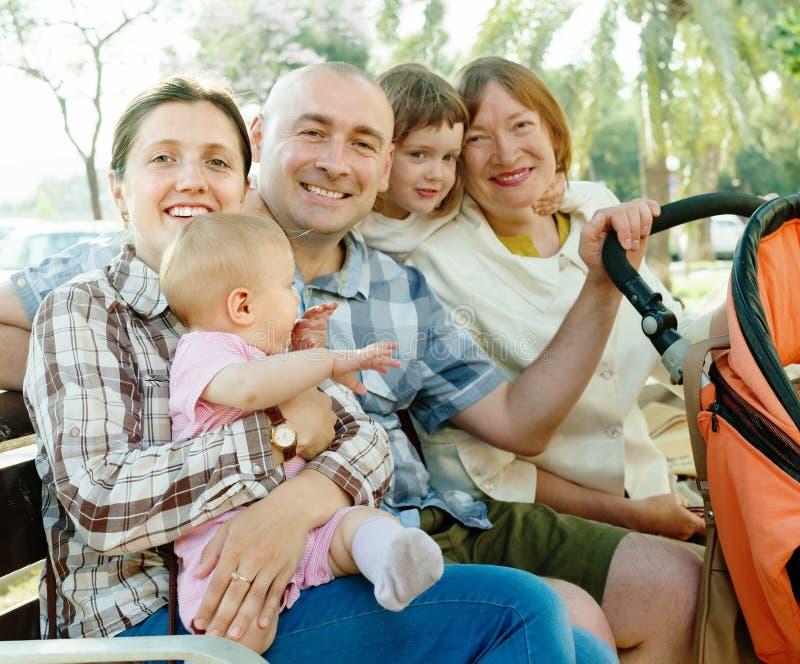 Счастливая семья 3 поколений сидя в парке стоковые изображения