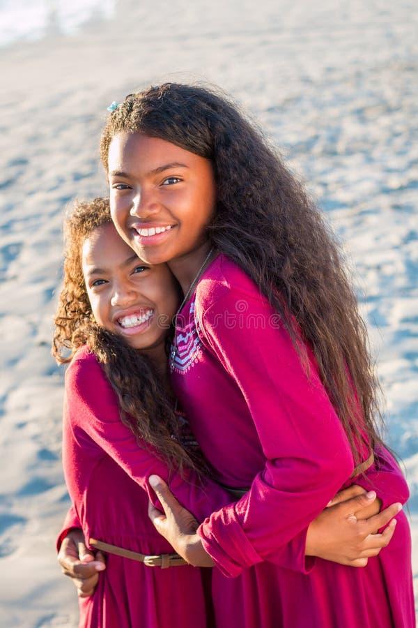 Счастливая семья, портрет 2 молодой сестер outdoors усмехаясь стоковое фото rf