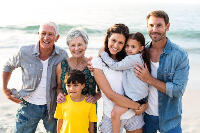 Счастливая семья представляя на пляже стоковое фото rf