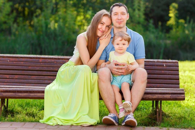 Счастливая семья при маленькая дочь сидя на стенде стоковые изображения