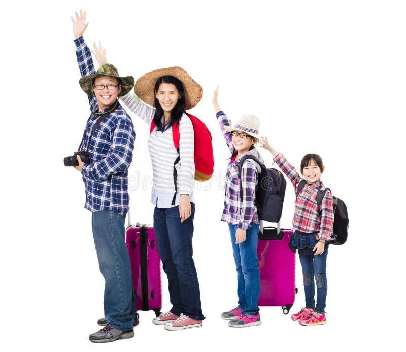 Счастливая семья при чемодан идя на каникулы стоковое изображение