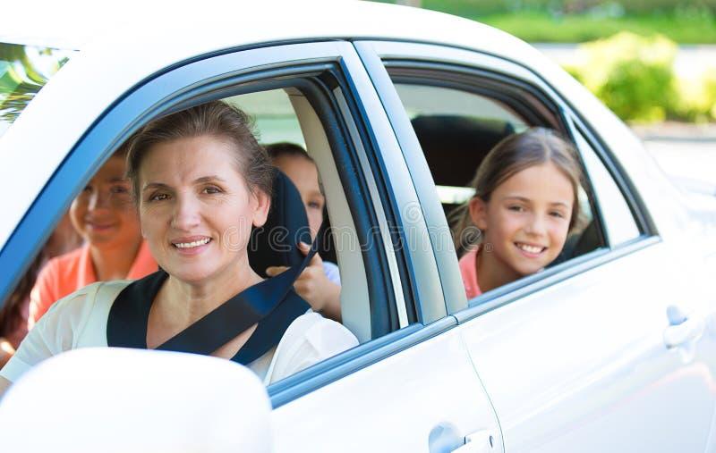 Счастливая семья сидя в автомобиле стоковое изображение rf